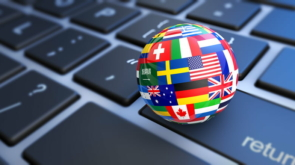 International business concept with a computer keyboard and world flags on a globe 3D illustration.